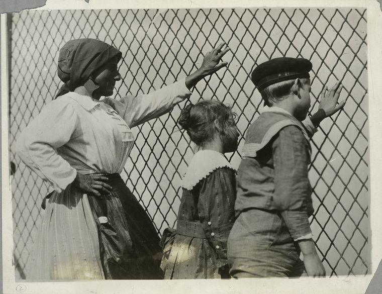 A family waits at a chain-link fence outside of Ellis Island.